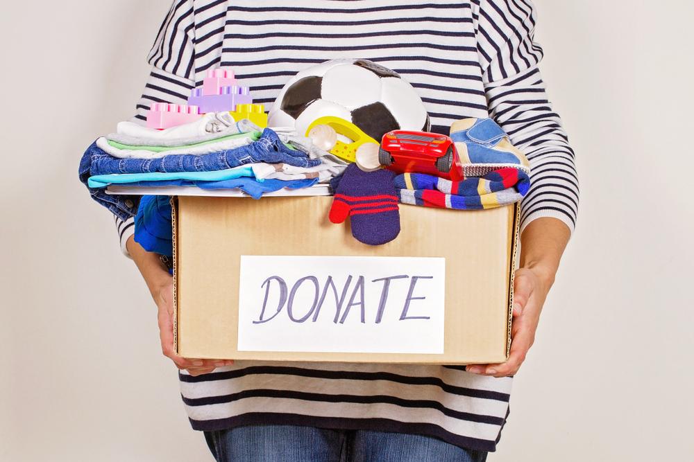 lady holding a donation box full of stuff