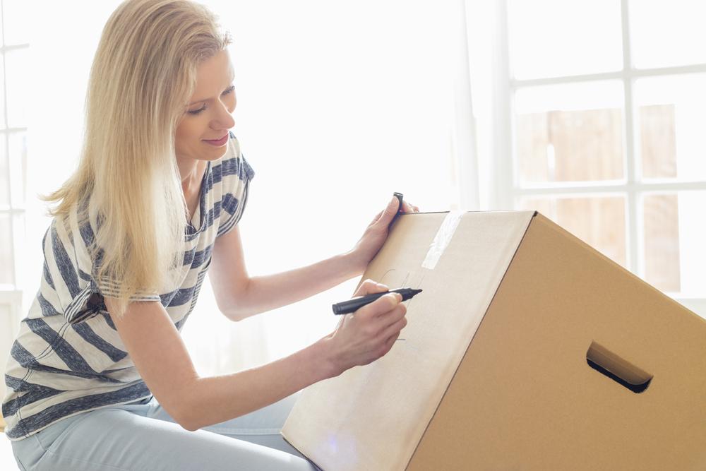 get organized! lady writing on a cardboard moving box