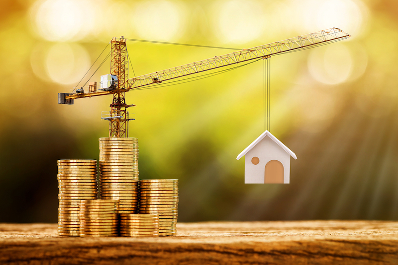 Coins and crane lifting up a tiny home is in reference to the construction loans in this article.