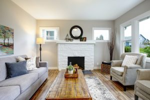 Traditional living room with white brick fireplace, symmetrical furniture layout and wood finishes.