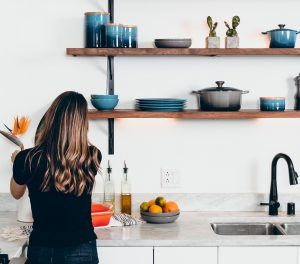 Woman unpacking her kitchen in her new custom home.