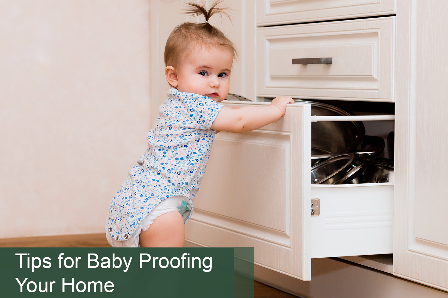 Baby girl in onesie opening kitchen cabinet; in need of baby proofing your home.