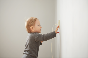 Baby playing with wall socket.