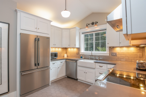 White square kitchen with new stainless steel appliances.