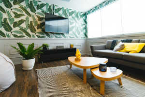 New home design that mixes form and function with funky green leaf wallpaper and large space in living room.