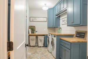 Laundry room in custom home with blue cabinets.