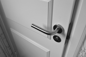 Silver door lever on a white door.