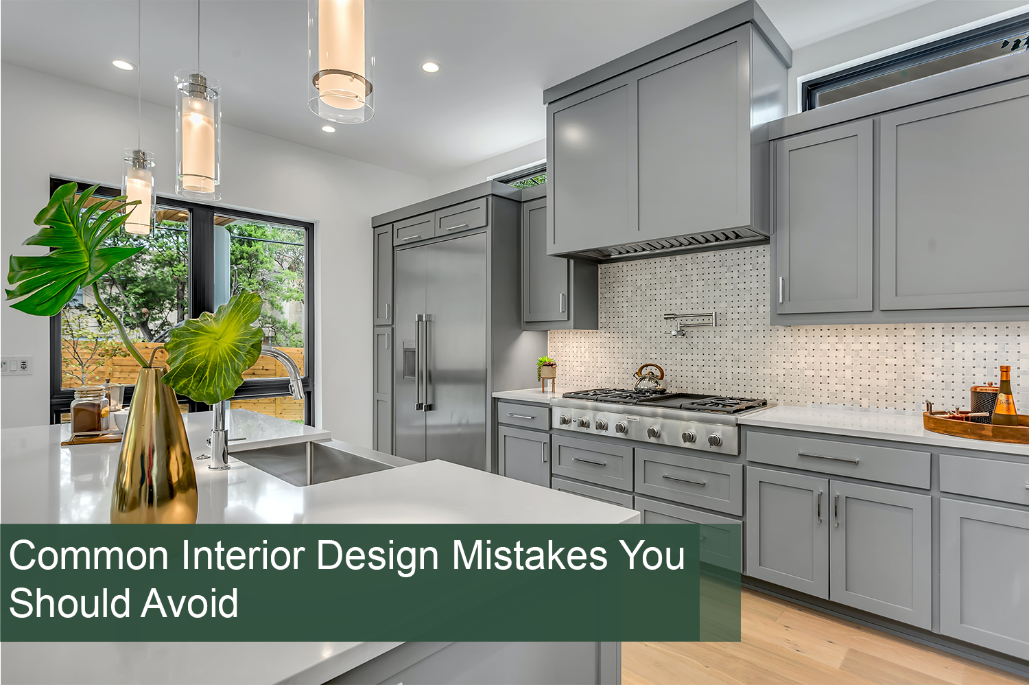 A kitchen with gray cabinets and pendant lights over the island - interior design mistakes have been avoided here.